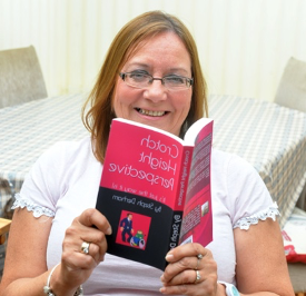 Steph Derham holding up her book