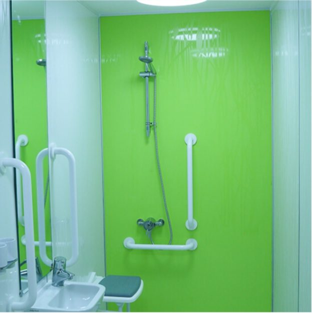 bathroom has a fully accessible wet room facility with nonslip flooring, low level seating under an adjustable shower wi